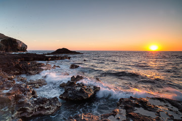 Colorful sunset at pristine untouched island destination in Mexico with beautiful breaking waves