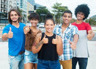 Jugendgruppe in der Stadt zeigt Daumen hoch
