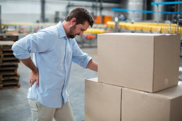 Tensed male worker standing with back pain
