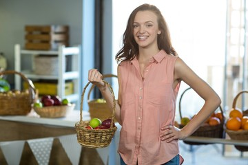 Smiling woman holding a basket of apples in the grocery store