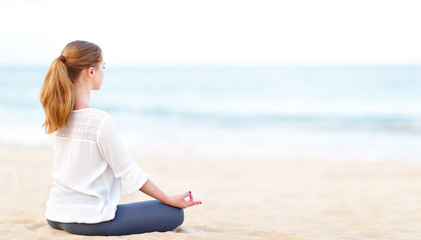 Fototapete - woman practices yoga and meditates in lotus position on beach