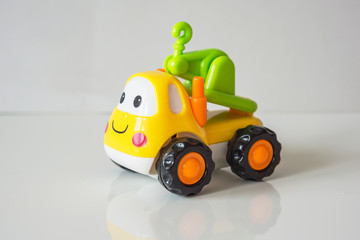 Colorful, children plastic toy, toy truck tractor with a smile and eyes. On a white background with reflection.