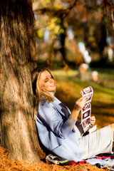 Young pregnant woman sitting in the autumn park