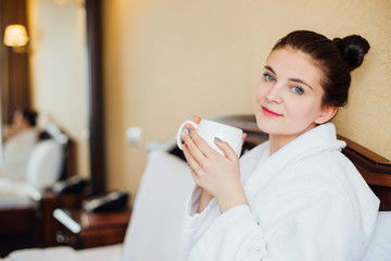 Young woman in a white bathrobe drinking tea or coffee on the bed in the hotel room