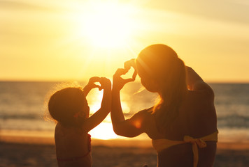 The concept of love, parenthood and happy family. Mother and child daughter show heart from hands at sunset