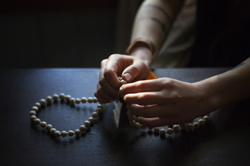 Cropped image of woman praying with beads in darkroom at home