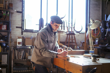 Confident carpenter planning wood on table in workshop