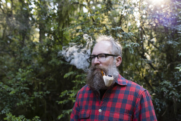 Man smoking pipe while standing against trees