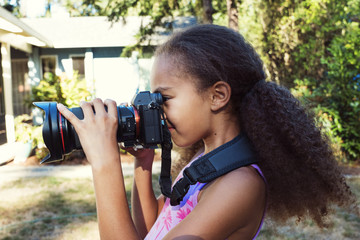 Side view of girl photographing through digital camera while standing in yard