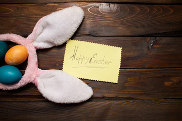 Pink bunny ears with Easter, colored eggs and the words Happy Easter on yellow piece of paper on the background deevyannom as postcards, posters, advertising