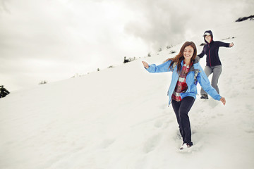 Female friends running down on snow covered mountain