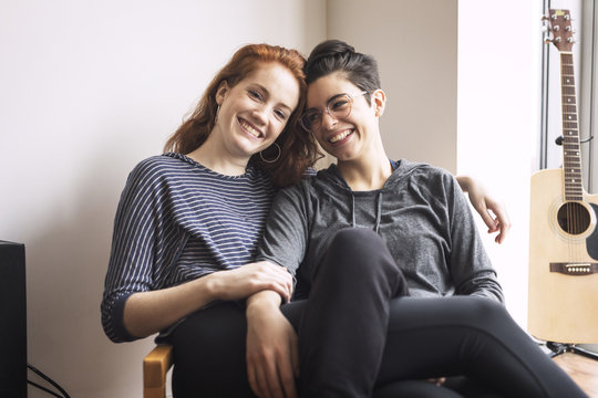 Happy lesbian couple sitting on chair at home