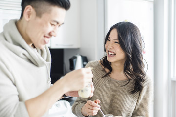 Cheerful couple eating breakfast in kitchen