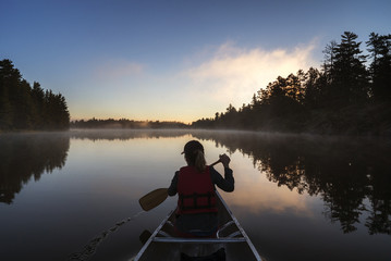 Rear view of woman traveling in boat on calm lake during sunset