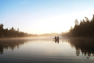 Man and woman traveling in boat on lake during foggy weather