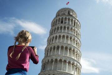 Rear view of girl photographing Leaning Tower of Pisa against sky