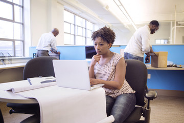 Businesswoman using laptop computer while male colleagues working in background