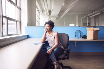Thoughtful businesswoman looking away while sitting on chair in office