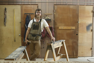 Portrait of confident carpenter with work tools standing in workshop