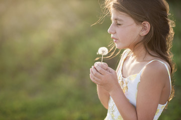 Side view of girl holding dandelion seed while standing on grassy field