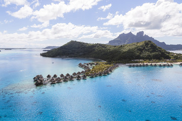 Aerial view of stilt houses by mountains at Bora Bora island