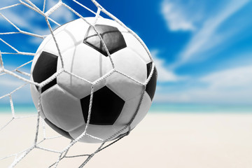soccer ball in goal net with tropical beach