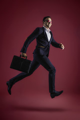 Business men running with suitcase on pink background