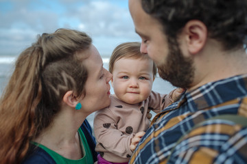 Portrait of baby girl being carried by parents at beach