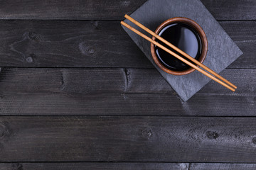 Background for sushi. Soy sauce, chopsticks on black stone. Top view with copy space