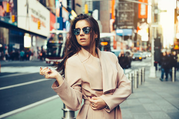Fashionable girl walking on New York City street in Midtown wearing sunglasses and ping jacket. Wall mural