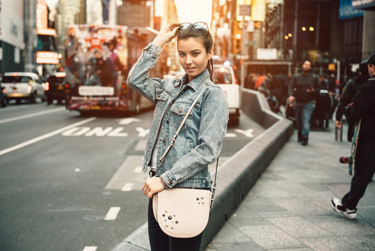 Lifestyle photo of happy young tourist adult woman looking at camera holding bag purse and sunglasses on sunny busy city street,