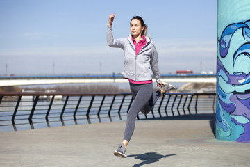 Morning exercise along the river. A young woman on recreation and jogging