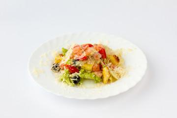 Салат с креветками. Креветки, помидор, маслины, листья салата посыпаны тертым твердым сыром