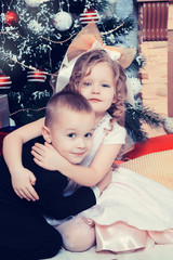 Boy and girl with gifts near the Christmas tree.