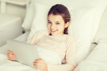 happy girl lying in bed with tablet pc at home
