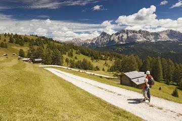 Hikers walk in the path of Utia Vaciara, South Tyrol, Dolomites, Italy