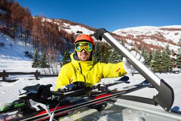 Sporty man unloading ski equipment from car roof