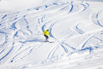 Sporty man skiing downhill in high mountains