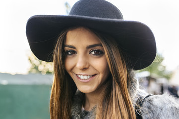 Portrait of smiling young woman wearing a hat