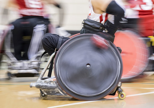 Wheelchair Rugby Player Moving Fast Across Gym Floor with Wheel Spinning