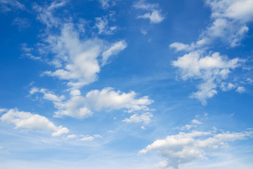 Blue sky with clouds over horizon. White clouds against blue sky.