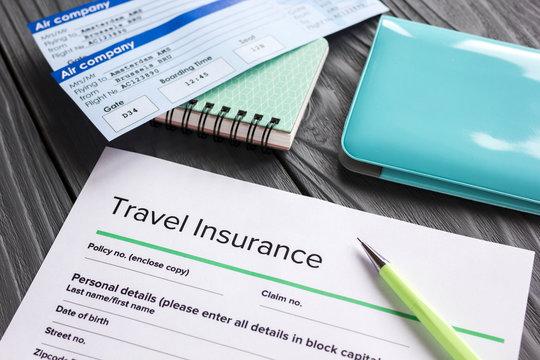 Travel insurance application form on wooden desk background