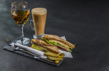 set consisting of two sandwiches malted bread with vintage cheddar cheese, pickles, red onion, tomato, lettuce, white wine and coffee latte