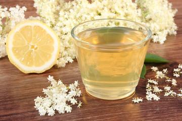 Fresh healthy juice, elderberry flowers and lemon on rustic board