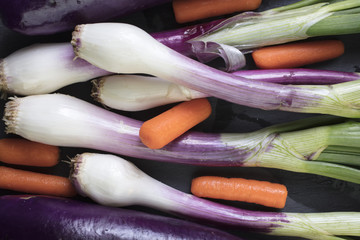 Poster Afrique du Sud Green onions, Carrots, Japanese Eggplant and Zucchini bunch together on a slate cutting board