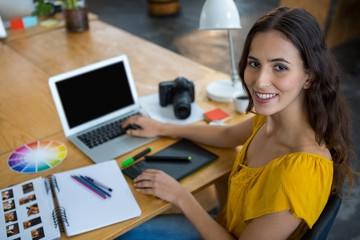 Smiling female graphic designer using laptop