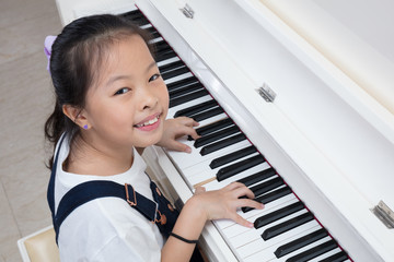 Happy Asian Chinese little girl playing classical piano at home