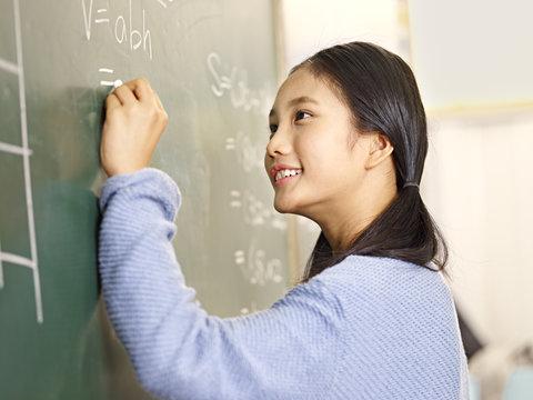 asian elementary school student solving a math problem