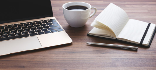 Office desk with laptop and coffee cup