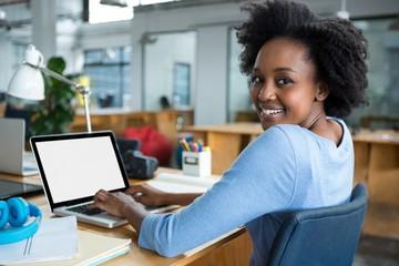 Female graphic designer using laptop in creative office